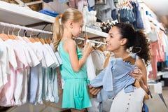 Женщина при малая девушка выбирая голубые одежды Стоковые Фотографии RF
