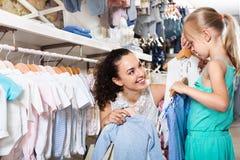 Женщина при малая девушка выбирая голубые одежды Стоковые Изображения