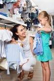 Женщина при малая девушка выбирая голубые одежды Стоковые Фото