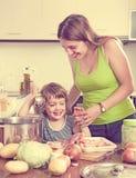 Женщина при маленькая девочка варя совместно Стоковое Изображение