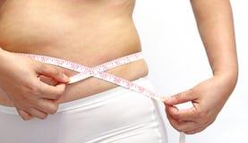Женщина при меньшее сало измеряя ее живот Стоковые Изображения