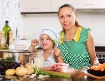 Женщина при младенец варя на кухне Стоковые Изображения