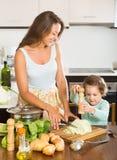 Женщина при младенец варя на кухне Стоковые Фотографии RF