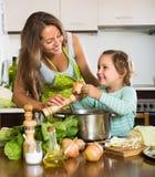 Женщина при младенец варя на кухне Стоковая Фотография RF