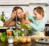 Женщина при младенец варя на кухне Стоковые Фото