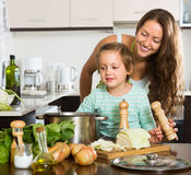 Женщина при младенец варя на кухне Стоковое Изображение RF