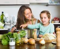 Женщина при младенец варя на кухне Стоковая Фотография