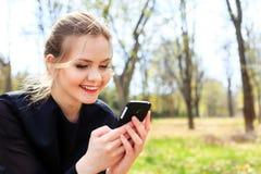 Женщина при неопрятные волосы смотря в усмехаться smartphone Стоковые Фотографии RF