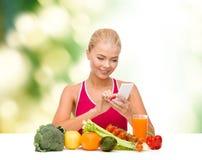 Женщина при овощи указывая на smartphone Стоковые Изображения