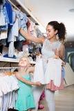 Женщина при дочь выбирая белые одежды младенца Стоковые Фото
