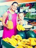 Женщина при дочь покупая различные плодоовощи в продовольственном магазине стоковая фотография