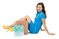 Женщина при пакеты сидя на поле стоковое изображение