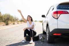 Женщина при прокалыванная покрышка автомобиля ища помощь стоковые фото