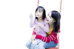 Женщина при ребенок играя на качании Стоковые Фото