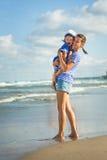 Женщина при ребенок играя на пляже Стоковые Изображения