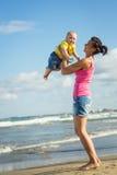 Женщина при ребенок играя на пляже Стоковое фото RF