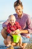 Женщина при ребенок играя на пляже Стоковые Фотографии RF