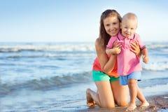 Женщина при ребенок играя на пляже Стоковое Фото