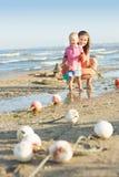 Женщина при ребенок играя на пляже Стоковые Изображения RF