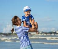 Женщина при ребенок играя на пляже Стоковая Фотография