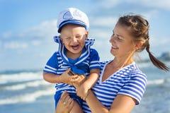 Женщина при ребенок играя на пляже Стоковые Фото