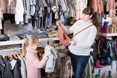 Женщина при ребёнок выбирая одежды Стоковые Фото