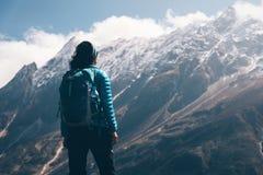 Женщина при рюкзак смотря на красивых горах Стоковое фото RF