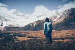 Женщина при рюкзак смотря на красивых горах Стоковое Фото