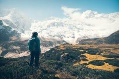 Женщина при рюкзак смотря на красивых горах Стоковое Изображение RF