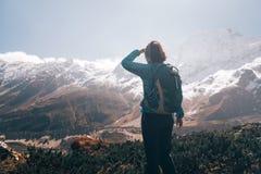 Женщина при рюкзак смотря на красивых горах Стоковая Фотография RF