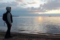 Женщина при рюкзак стоя на речном береге на заходе солнца Стоковая Фотография RF