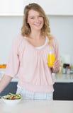 Женщина при салат держа апельсиновый сок в кухне Стоковые Изображения