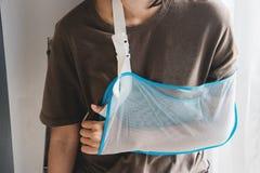 Женщина при сломленная рука нося слинг руки Женщина нося руку стоковые изображения