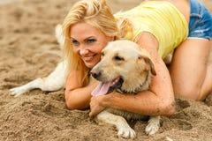 Женщина при собака играя на пляже Стоковое Изображение RF