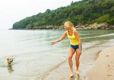 Женщина при собака играя на пляже Стоковые Изображения RF