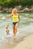 Женщина при собака играя на пляже Стоковое Изображение