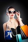 Женщина при стекла держа хозяйственные сумки против черной предпосылки Стоковая Фотография