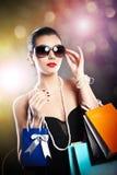 Женщина при стекла держа хозяйственные сумки против черной предпосылки Стоковые Изображения