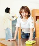 Женщина при супруг очищая деревянное furiture с ветошью Стоковые Изображения RF