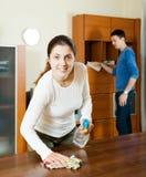 Женщина при супруг очищая деревянное furiture Стоковая Фотография