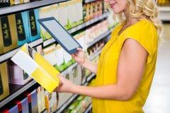 Женщина при таблетка держа коробку Стоковая Фотография