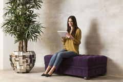 Женщина при таблетка сидя на софе Стоковое фото RF