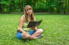 Женщина при таблетка сидя на траве в парке Стоковые Изображения RF