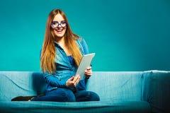 Женщина при таблетка сидя на цвете сини кресла Стоковая Фотография