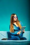 Женщина при таблетка сидя на цвете сини кресла Стоковая Фотография RF