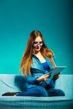 Женщина при таблетка сидя на цвете сини кресла Стоковые Изображения RF