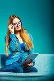 Женщина при таблетка сидя на цвете сини кресла Стоковое фото RF