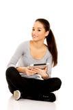 Женщина при таблетка сидя перекрестное шагающее Стоковая Фотография