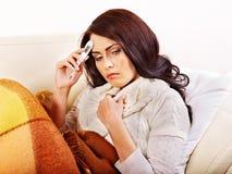 Женщина при термометр имея газоход в кровати. Стоковые Фото