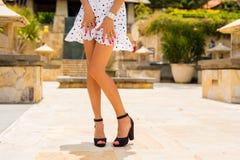 Женщина при тонкие сексуальные ноги представляя в белом платье лета и черных высоких пятках стоковые изображения rf